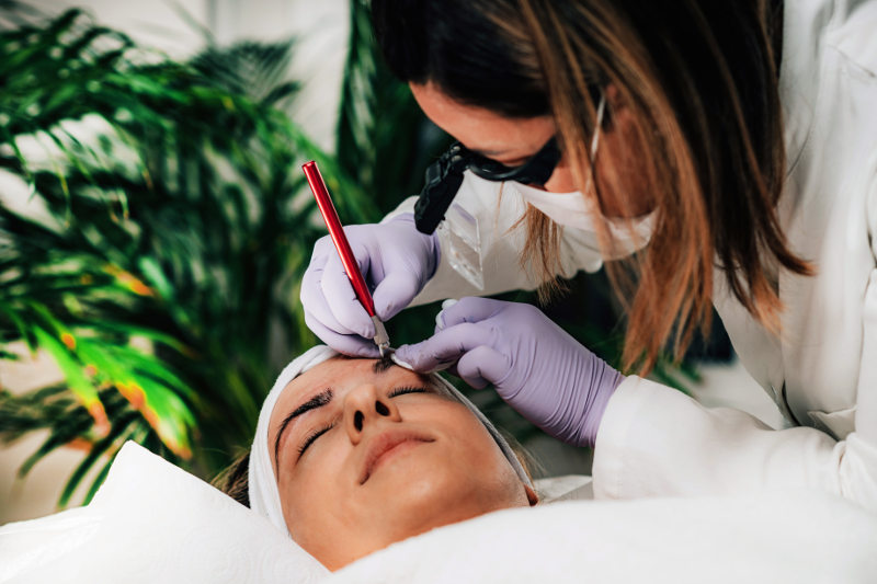 Beautician Microblading Eyebrows in Beauty Salon